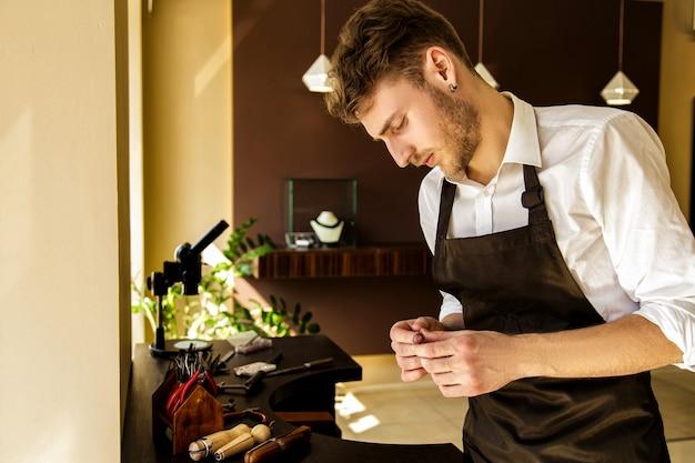 Um joalheiro está olhando para o anel perto da mesa