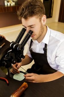 Um joalheiro examina cuidadosamente a pedra para criar um anel através de um microscópio