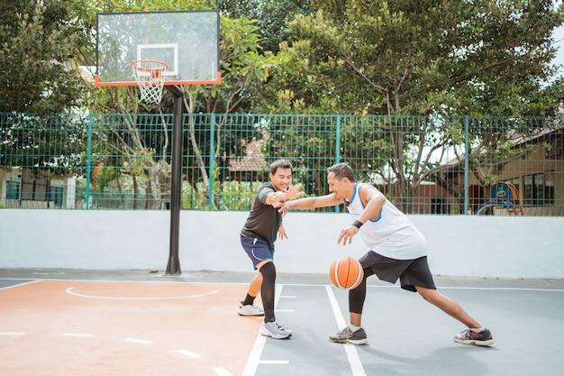 Um jogador de basquete carregando a bola é bloqueado pelos jogadores oponentes