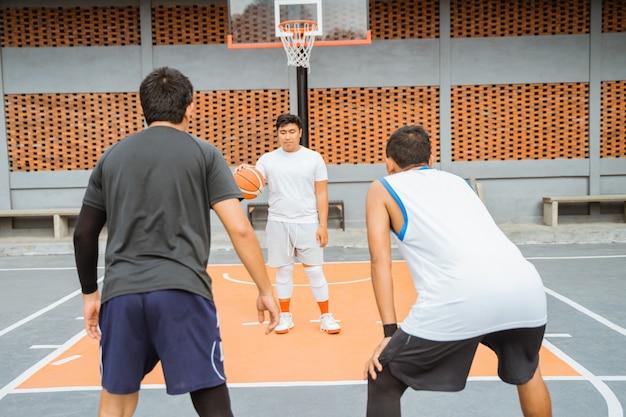 Um jogador de basquete carregando a bola é bloqueado por dois jogadores adversários em uma posição pronta