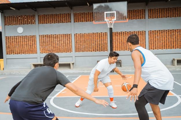 Um jogador de basquete com um agasalho esportivo branco dribla a bola na cara de dois jogadores adversários