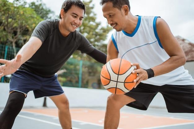 Um jogador de basquete executa um drible baixo quando confrontado por um jogador adversário