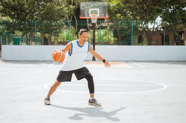 Um jogador de basquete fazendo um drible alto com a bola enquanto pratica basquete