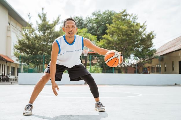 Um jogador de basquete fazendo um drible baixo com a bola enquanto pratica