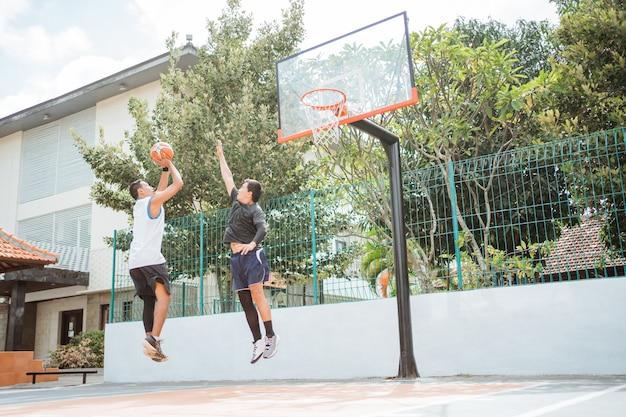 Um jogador de basquete masculino dá um arremesso contra um oponente
