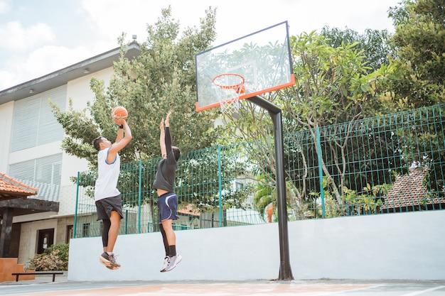 Um jogador de basquete masculino dá um arremesso e é bloqueado por seu oponente com as duas mãos