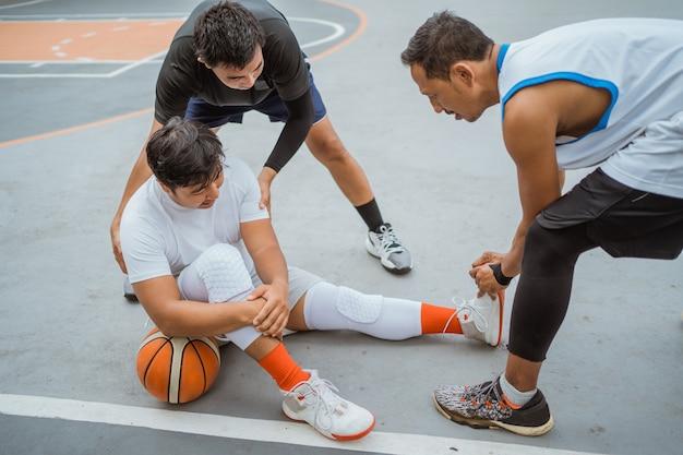 Um jogador de basquete senta no chão devido a uma cãibra muscular e é ajudado por outro jogador