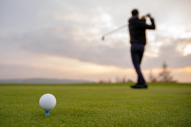 Um jogador de golfe prepara a bola para ser disparada no campo de golfe