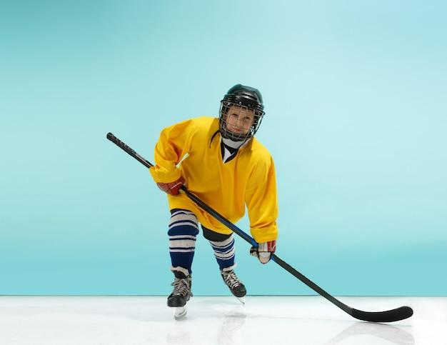 Um jogador de hóquei de uniforme com equipamento sobre um fundo azul do estúdio. o atleta, criança, esporte, conceito de ação