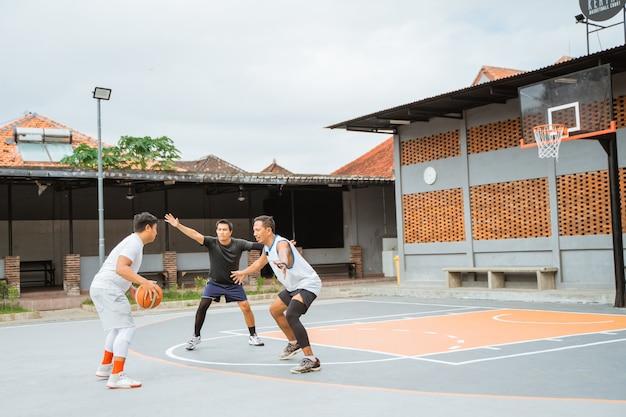 Um jogador driblando a bola vai atacar e dois jogadores adversários ficam no caminho