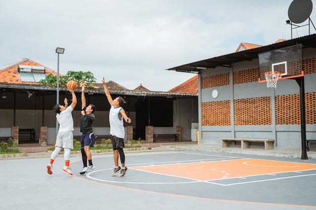 Um jogador que salta atirará em três pontos e dois defensores pularão no bloco com as mãos