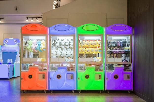 Um jogos de máquina de garra multicolor em loja de departamento.