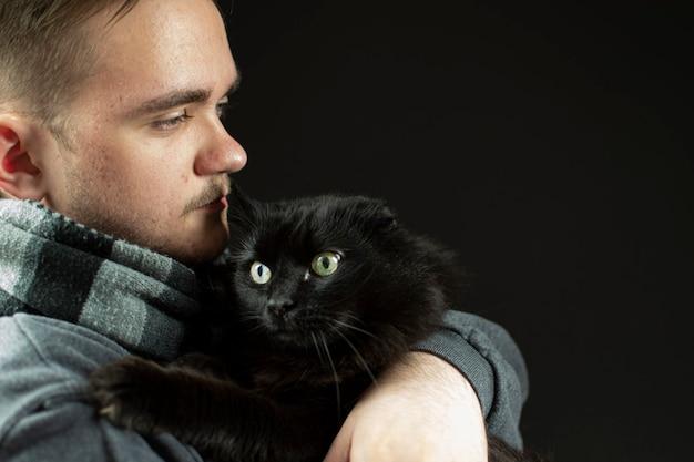 Um jovem adulto abraça um gato, um homem com um cachecol preto, um gato preto nos braços do homem