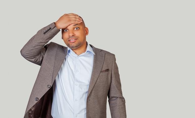 Um jovem afro-americano com uma expressão assustada segura a mão na testa. cara com uma expressão culpada
