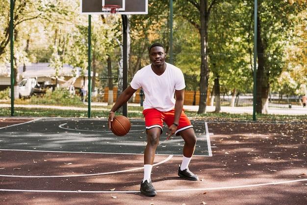 Um jovem afro-americano está jogando basquete em uma quadra ao ar livre, sorrindo e olhando para a câmera. esportes ao ar livre.