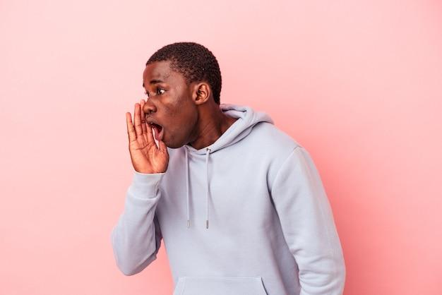 Um jovem afro-americano isolado em um fundo rosa está contando uma notícia secreta sobre a travagem e olhando para o lado