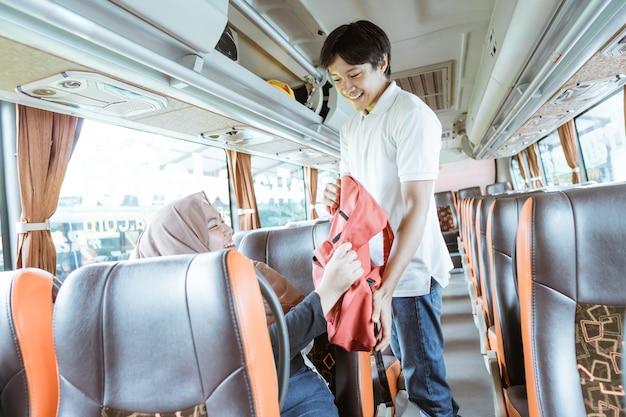 Um jovem ajuda uma mulher com véu a colocar sua bolsa em uma prateleira enquanto está de pé no ônibus