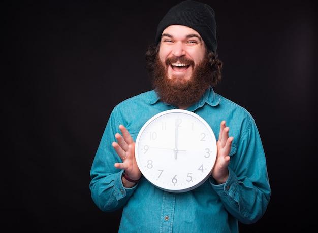 Um jovem alegre está sorrindo para a câmera e segurando um grande relógio branco redondo com as duas mãos perto de uma parede preta