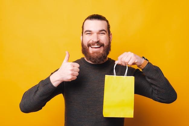 Um jovem alegre mostra que gosta de ir às compras com um saco de papel nas mãos