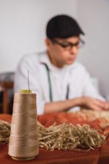 Um jovem alfaiate trabalhando em sua pequena oficina de costura.