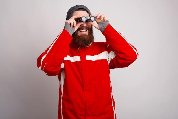 Um jovem alpinista barbudo está sorrindo e olhando através do binóculo.
