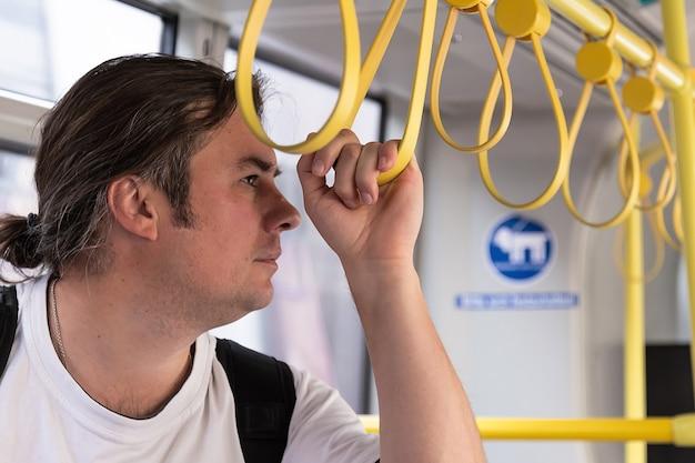 Um jovem anda no transporte público terrestre urbano segurando-se nos corrimãos amarelos.