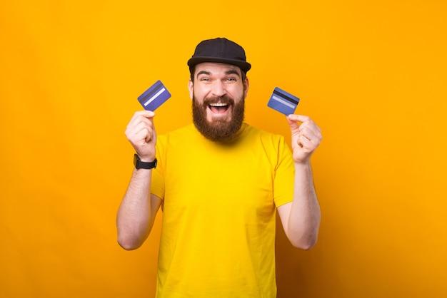 Um jovem animado está segurando dois cartões de crédito, olhando para a câmera