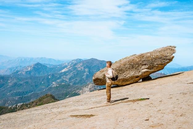 Um jovem ao lado de uma pedra pendurada em uma rocha no parque nacional de sequóia eua