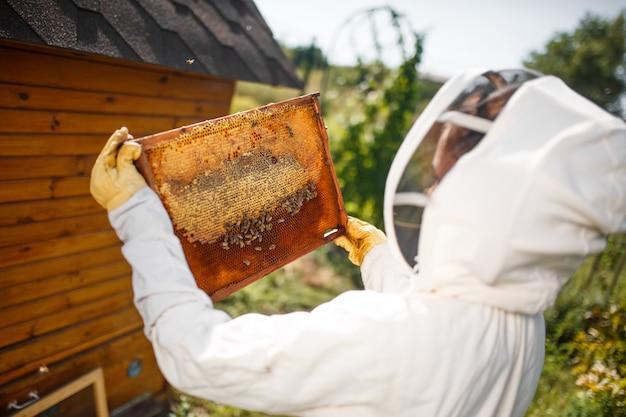 Um jovem apicultor feminino em um traje profissional de apicultor