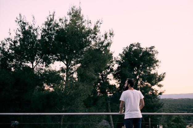 Um jovem apreciando a paisagem em sua casa na floresta