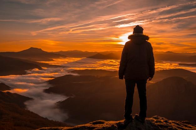 Um jovem apreciando o nascer do sol de peñas de aia. país basco