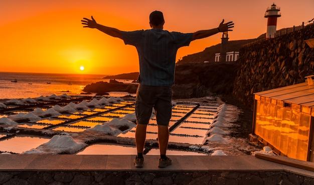 Um jovem apreciando o pôr do sol no farol de fuencaliente ao lado da mina de sal, na rota dos vulcões ao sul da ilha de la palma, nas ilhas canárias, espanha