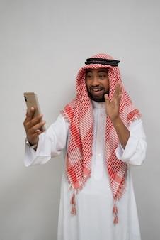 Um jovem árabe de turbante faz uma videochamada usando um telefone celular enquanto sorri com um gesto de mão