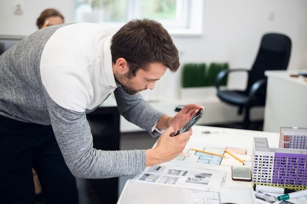Um jovem arquiteto tirando fotos do modelo de construção enquanto estava no escritório