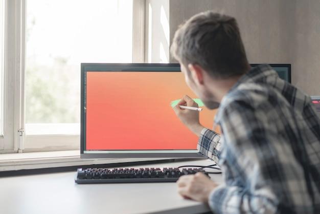 Um jovem artista digital masculino desenhando tinta na tela do computador em estúdio