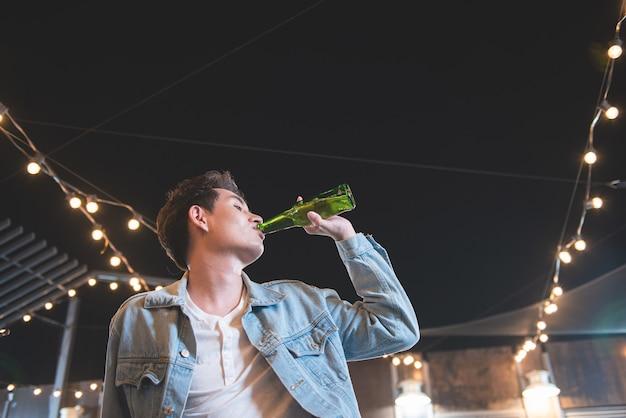 Um jovem asiático beber garrafa de cerveja. a vista lateral dos homens bonitos hipster mão segurando a garrafa e a bebida de cerveja enquanto está sentado no balcão de bar no piso do último piso da festa da boate no restaurante.