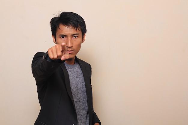 Um jovem asiático bonito curioso e direto apontando em você, vestindo um terno com uma camisola