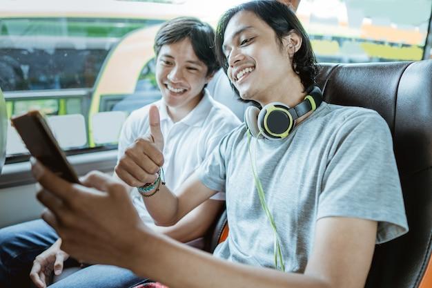Um jovem asiático com fones de ouvido e usando um telefone celular para videochamadas com o polegar para cima enquanto está sentado perto de uma janela em um ônibus