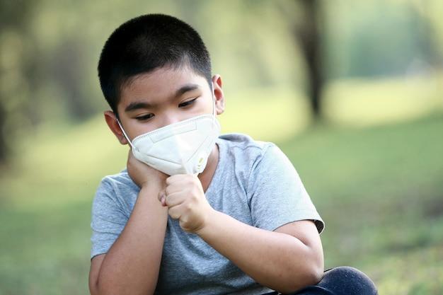 Um jovem asiático de 7 anos usa máscara para proteger contra poeira pm 2.5 e germes