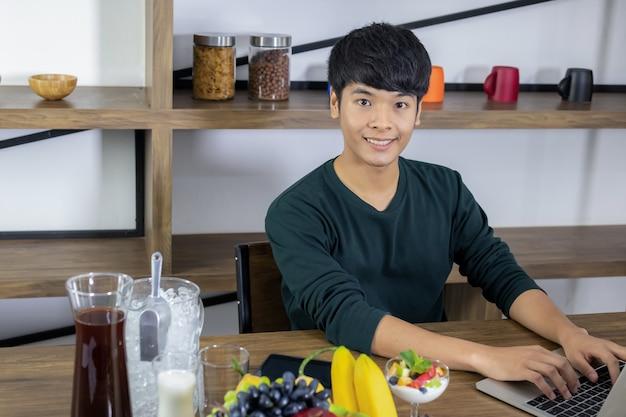 Um jovem asiático está trabalhando em um negócio para o notebook e olhando para o iogurte de frutas no restaurante moderno.