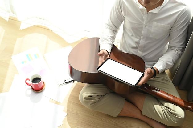 Um jovem asiático está usando um tablet e uma guitarra enquanto está sentado no chão da sala de estar