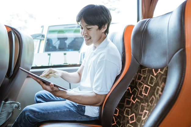 Um jovem asiático usando um tablet enquanto está sentado no ônibus