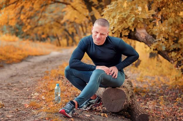Um jovem atleta atlético, vestindo roupas esportivas pretas e tênis, senta-se em um tronco e sente uma forte dor no músculo após uma cãibra