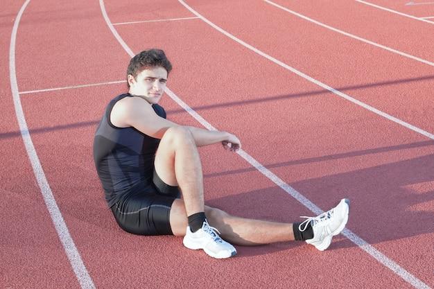 Um jovem atleta faz alongamento. no contexto da esteira.