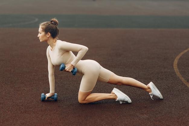 Um jovem atleta treina com halteres no estádio. o conceito de uma vida ativa saudável.