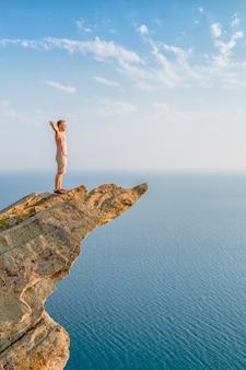 Um jovem atlético fica em um pitoresco penhasco íngreme acima do mar contra o céu