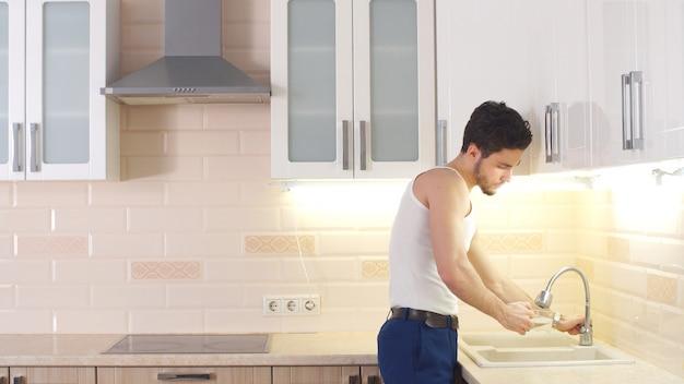 Um jovem atraente derrama água da torneira em um copo na cozinha