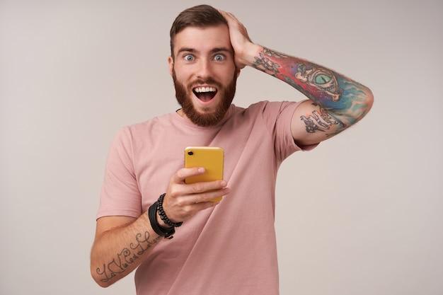 Um jovem barba por fazer de olhos azuis feliz com tatuagens segurando a cabeça com a mão levantada com rosto surpreso, isolado no branco