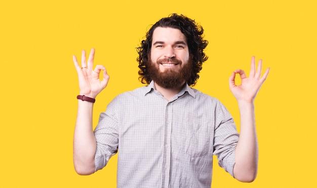 Um jovem barbudo alegre está sorrindo para a câmera, sentado em uma pose zen perto de uma parede amarela