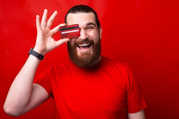 Um jovem barbudo alegre segurando um cartão de crédito perto do olho e sorrindo